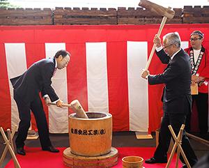出発式でもちつきをする佐藤元社長(左)
