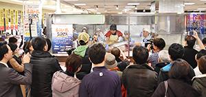 宇和島水産高校「フィッシュガール」による完全養殖クロマグロ解体ショーは、多くの見学者でにぎわった(写真は18日・中島水産玉川高島屋店)