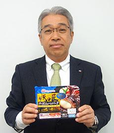 好調「焼の匠チーズ入りハンバーグ」を手に鶴田道太社長
