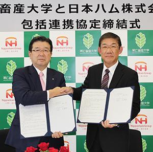 末澤壽一・日本ハム社長(左)と奥田潔・帯広畜産大学学長