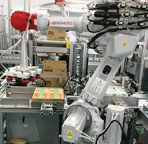 味の素社川崎事業所にある味の素パッケージング関東包装工場では、箱詰めロボットによって中装(ボール)詰めされた製品を外装の段ボールに詰める工程を自動化した(提供写真)