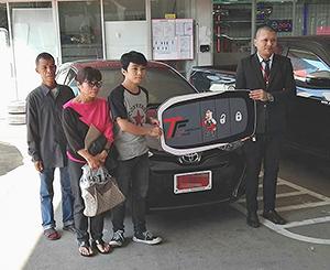 うま食堂で得た給料を積み立て、新車を購入した従業員のペック君(中央)。左側はチャイヤプーム県で暮らす両親=提供写真