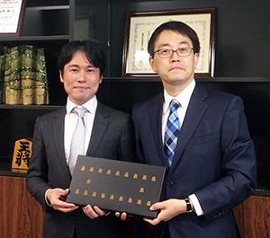 将棋チョコを持つ羽生善治竜王(右)と戸村憲人代表取締役