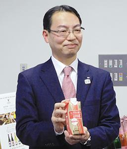 新商品の「ボタ・ミニ」を手に持つ福北耕一マーケティング第四部長