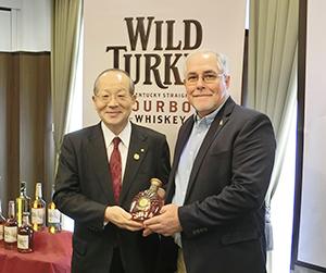「ワイルドターキーケンタッキースピリット」を持つ松沢幸一明治屋社長(左)とエディー・ラッセル氏