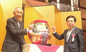 ダルマの目入れを行う高野正晴社長(左)と鈴木雅治三桜会会長