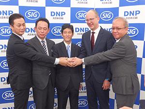 合弁会社設立に向けて握手をする大日本印刷の北島義斉副社長(中央)とSIG社のロルフ・シュタングCEO(右から2人目)ら