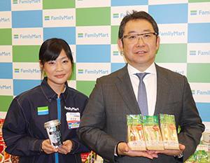 全粒粉入りパン使用のサンドイッチを手にする佐藤英成常務執行役員(右)