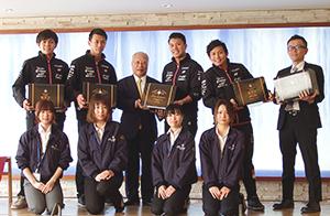後列、和田泰治会長(中央)と選手たち