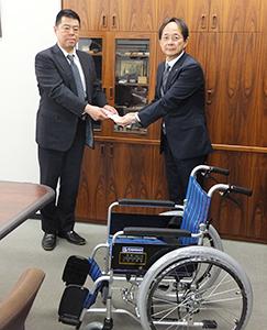 浅井俊之事務局長(右)に目録を手渡す房川雅一副理事長