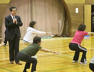 町田修一氏(左)の指導によってスクワットを行う参加者たち