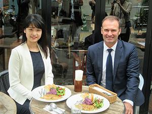カフェで提供するメニューと森恵愛PM(左)、ジョン・フォスCEO