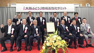 共同宣言文を囲んでガッツポーズの関係者(前列左から3人目が高井利洋大阪ワイナリー協会会長)