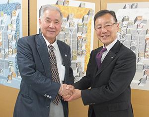 握手をする美濃吉食品の大西常昭社長(右)とアビーの大和田哲男社長