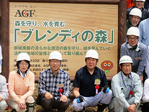 設置した看板を背に、品田英明社長(左から2人目)と山本龍市長(同3人目)