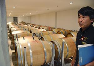 樽貯蔵庫について説明するMOGの1人、眞杉茂央氏。庫内はワイン樽の香りが感じられる