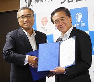 神奈川県庁で覚書を結び、握手する岸上克彦社長(左)と黒岩祐治神奈川県知事