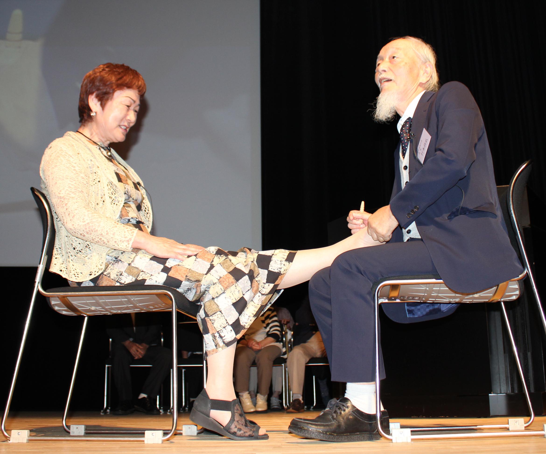 行本昌弘・官足法友の会会長(右)による足もみ施術