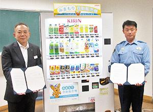 「みまもり自販機」を背にする新井裕明執行役員(左)と福山隆夫署長