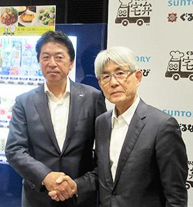 「宅弁」仕様自販機を背に握手する土田雅人社長(左)と久保征一郎ぐるなび社長