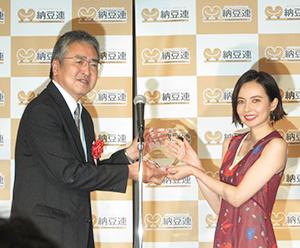 野呂剛弘納豆連会長(左)からトロフィーを贈呈されたベッキー
