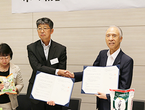 協定調印式で握手する雑賀慶二東洋ライス社長(右)と庭野吉也東都生協理事長