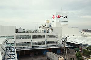 JR予讃線・伊予市駅、伊予鉄道・郡中港駅より徒歩7分、「花かつお通り」と名付けられた駅前から続くメイン道路沿いに立つヤマキ愛媛事業所 本社工場