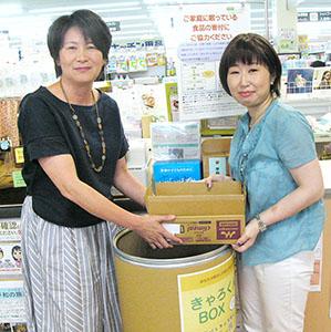 回収ボックスを持つフードバンクふなばし代表の笹田明子さん(左)