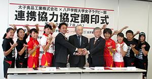 協定調印式で工藤茂雄社長(中央)と女子部員ら