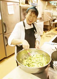 厨房でサラダを作る井出和代さん