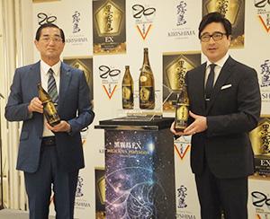 黒霧島EXを持つ江夏拓三専務(左)とジョン・カビラ