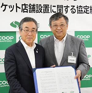 協定書を手にする大見英明理事長(右)と大野幸孝町長