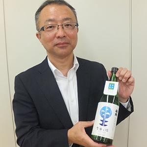 「梅錦 里海の環」を手にする藤原康展代表取締役
