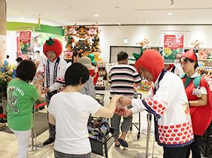 かぶり物を身に着け、来店者に配る石井俊樹カスミ社長(左から2人目)と大滝恭伸執行役員(右から2人目)