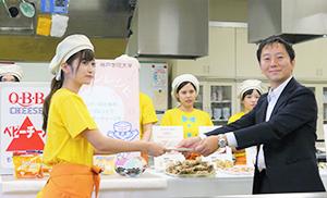 チーズを使用し、優秀なレシピを考案した学生を表彰する塚本浩康六甲バター取締役副社長開発本部長(右)