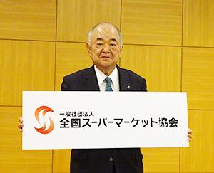 名称変更の「一般社団法人全国スーパーマーケット協会」のボードを手にする横山清会長