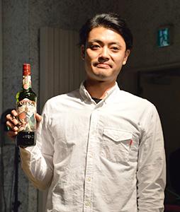 自身がデザインした日本限定ボトルを手に持つ、YU SUDA氏(11日、東京都港区)