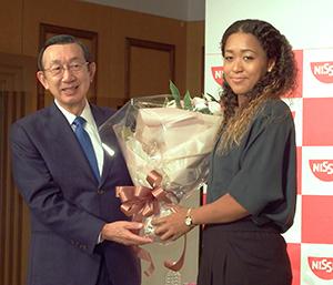 大坂なおみ選手に花束を渡す日清食品ホールディングスの安藤宏基社長・CEO(左)