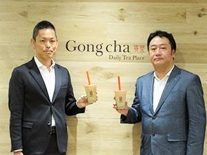「ほうじ茶 ミルクティー」を手に葛目良輔社長兼COO(左)と加藤重樹カクニ茶藤代表取締役