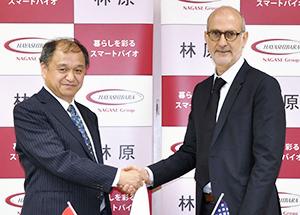 握手を交わす安場直樹社長(左)とエラスモ・シュッツアープレジデント