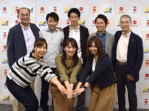 佐古則男社長(後列左端)、田中稔取締役業務本部長(同右端)と若手社員