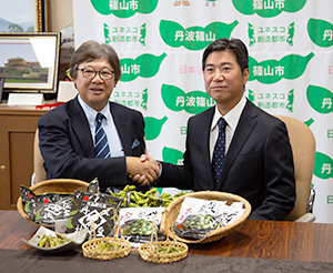 握手するケンミン食品高村一成社長(左)と小田垣商店小田垣昇常務