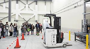 従業員とその家族は自動冷凍倉庫を間近で見学