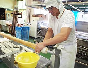 3回巻を作る宮村孝社長、長さ2mの金属棒に生地を巻き付けて繰り返し焼き上げる