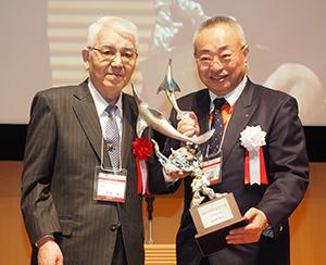 池田弘理事長(右)から正賞のシュプリンゲンが授与される大賞の荒井綜一氏