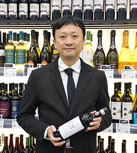 「イオンワインアワード2018」の受賞ワインを手に持つ、イオンリカーの加藤修一ワイン事業統括部部長
