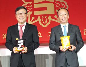 リニューアルした「スコーン」を持つ小池孝会長(右)と佐藤章社長