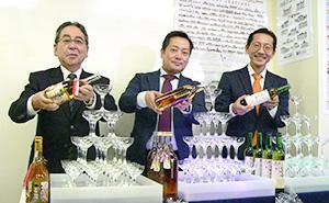 梅酒タワーにそれぞれの新酒を注ぐ、左から加藤高藏明利酒類社長、中野幸治中野BC社長、金谷優梅酒研究会専務理事(澤田酒造代理)