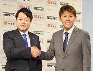 握手する西山知義会長(右)と新井田昇社長