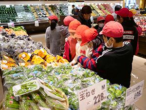 「買物ゲーム」で指定金額内で必要な食材を選ぶ児童たち(スーパーアルプスはざま店で)